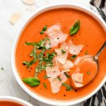 A bowl of Creamy Tomato Soup garnished with fresh basil and shaved Parmesan cheese.