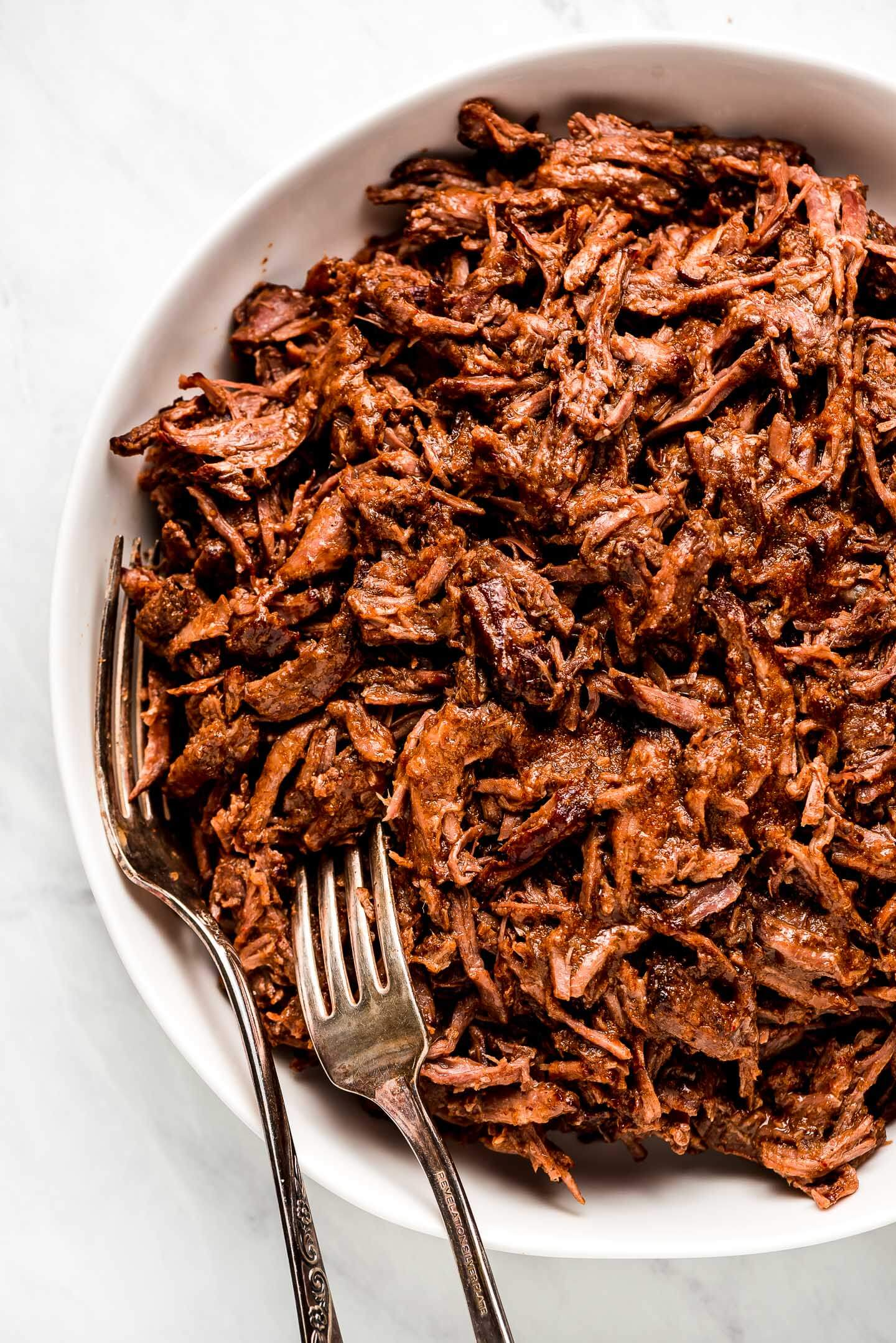 A serving bowl of shredded Slow Cooker Barbacoa Meat.