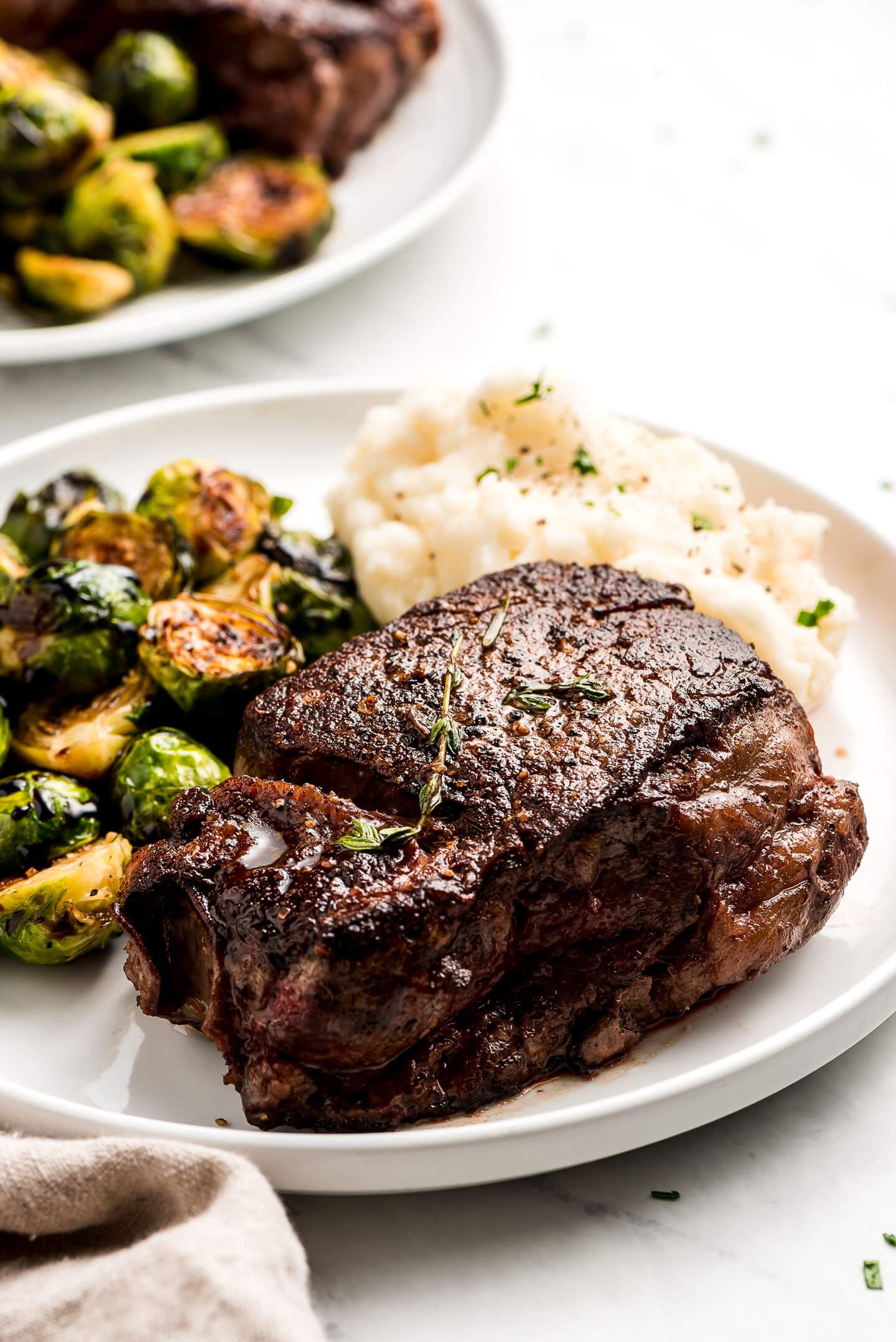 Filet Mignon, brussels sprouts, and mashed potatoes on a plate.