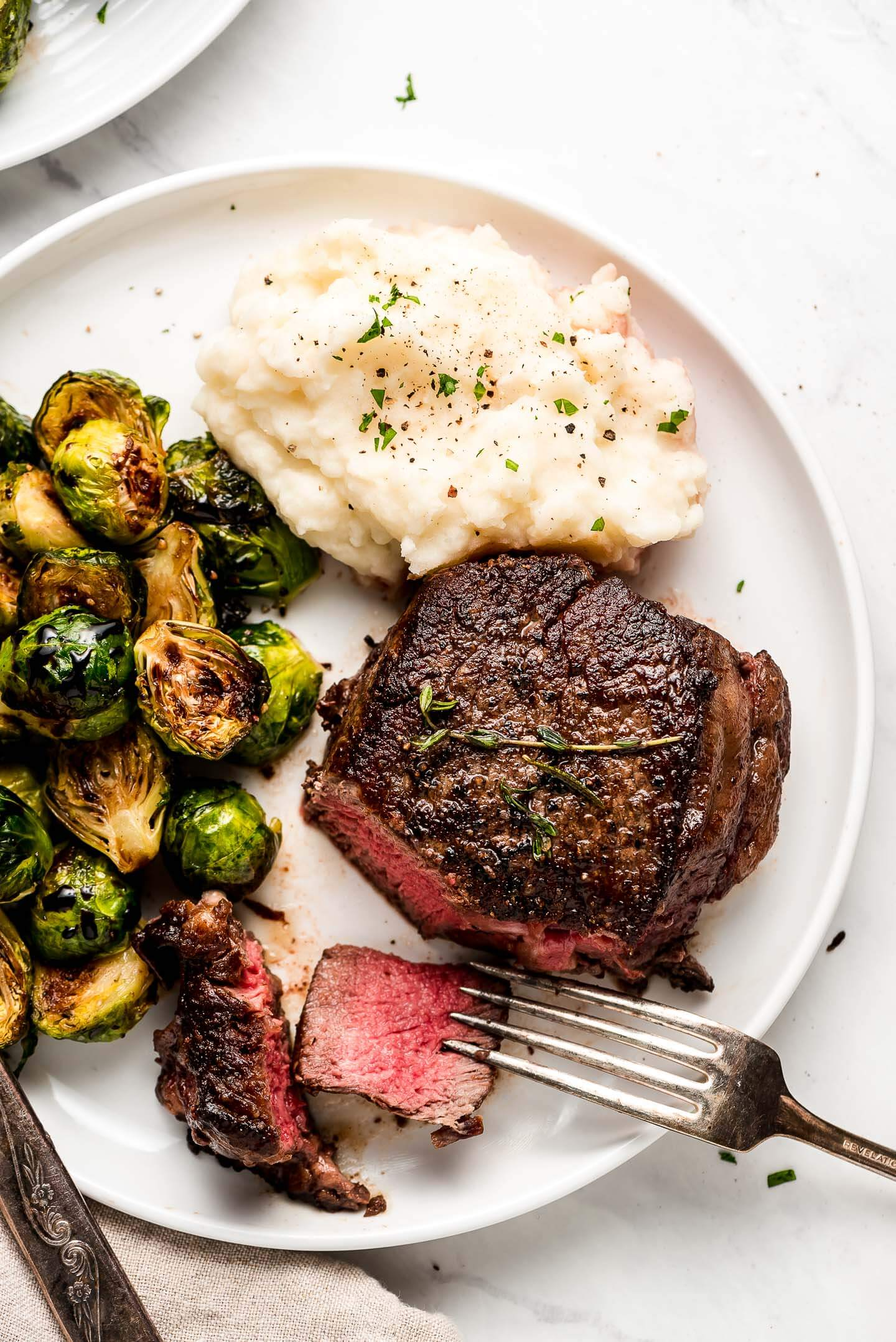 Steak, mashed potatoes, and brussels sprouts on a plate.