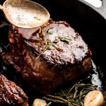 Spooning melted butter over a filet mignon in a cast iron skillet.