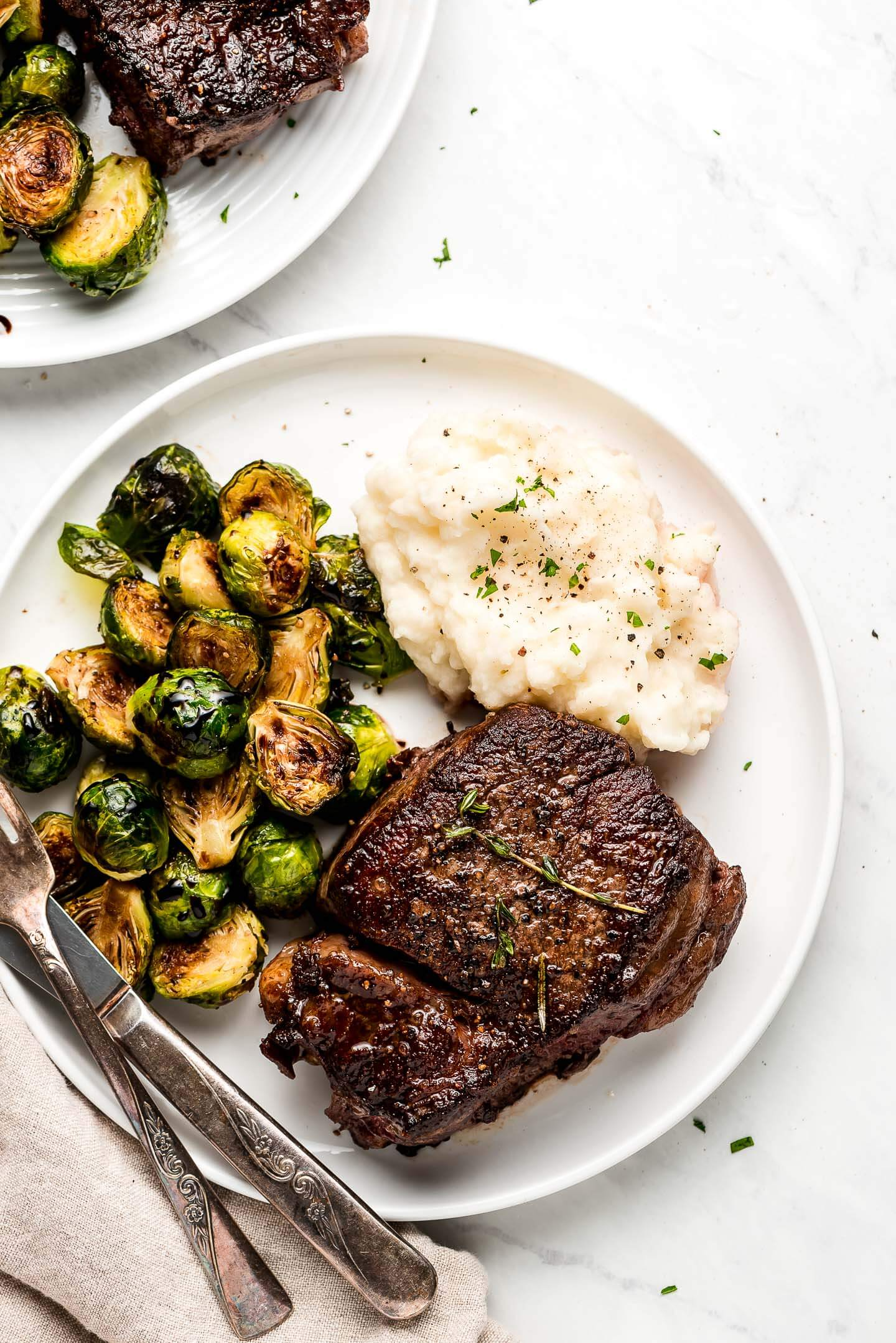 Filet Mignon Steak, mashed potatoes, and roasted brussels sprouts on a plate.