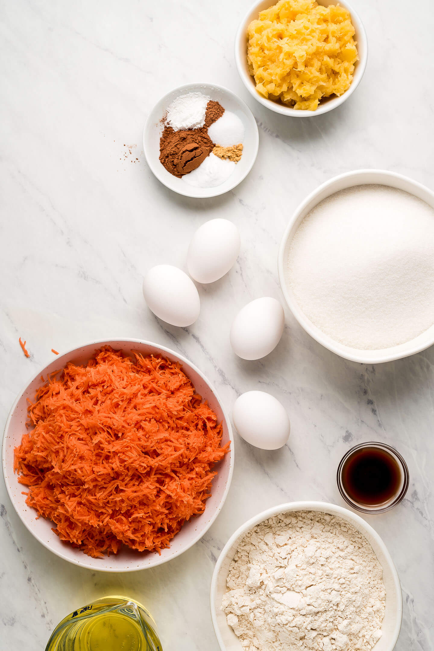 Ingredients on a marble surface- crushed pineapple, spices, eggs, sugar, shredded carrots, vanilla extract, flour, and oil.