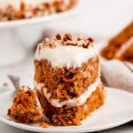 A slice of Moist Easy Carrot Cake on a plate with a fork full on the side.