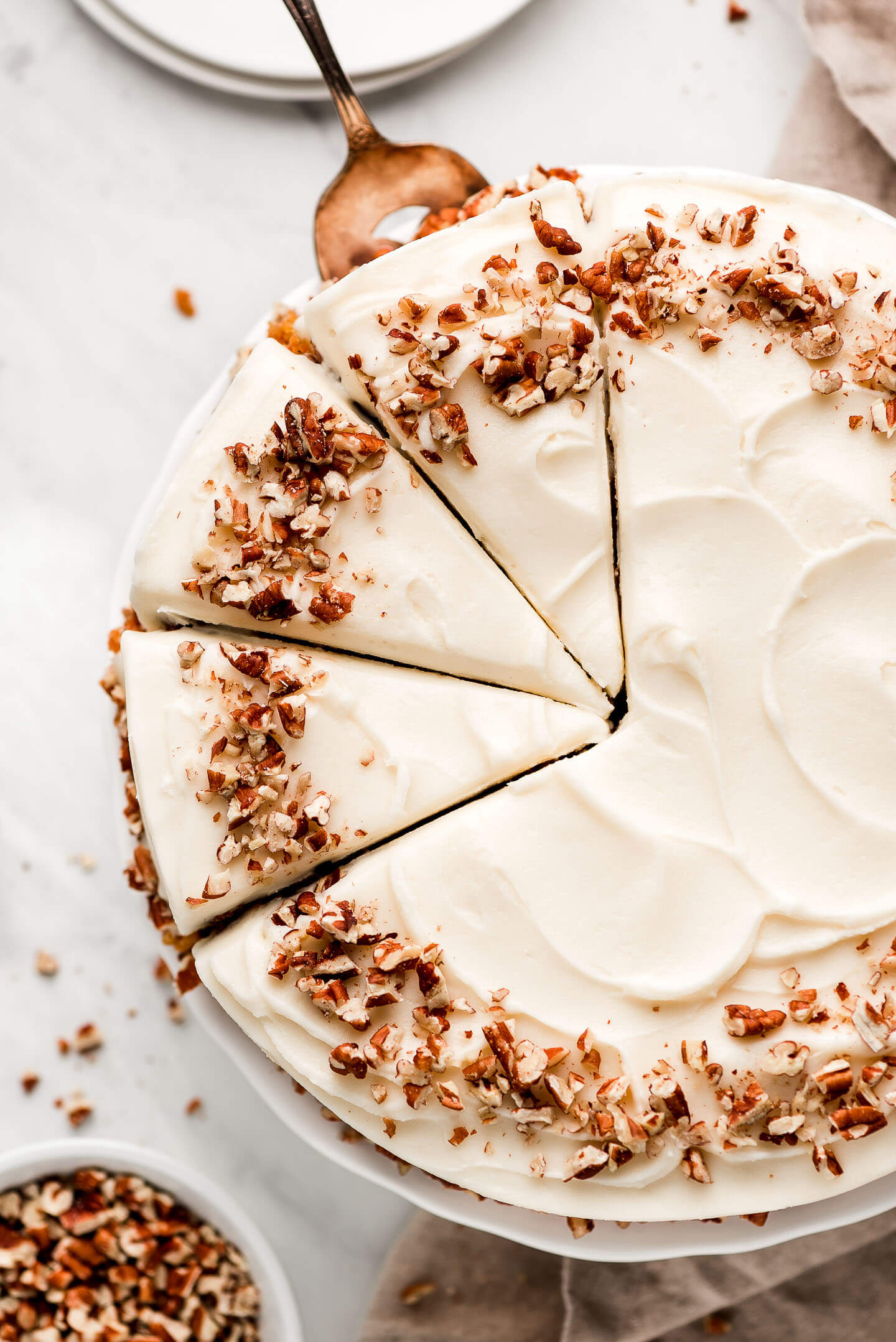 Top view of a sliced Carrot Cake frosted with cream cheese buttercream frosting and garnished with chopped toasted pecans.
