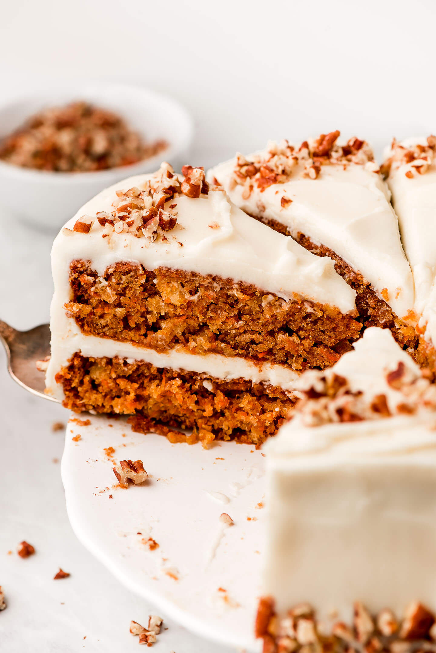 A slice of Easy Carrot Cake being removed from the cake stand.