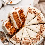 A Carrot Cake garnished with pecans and sliced into wedges; a slice to the side on a plate and pecans in a bowl to the side.