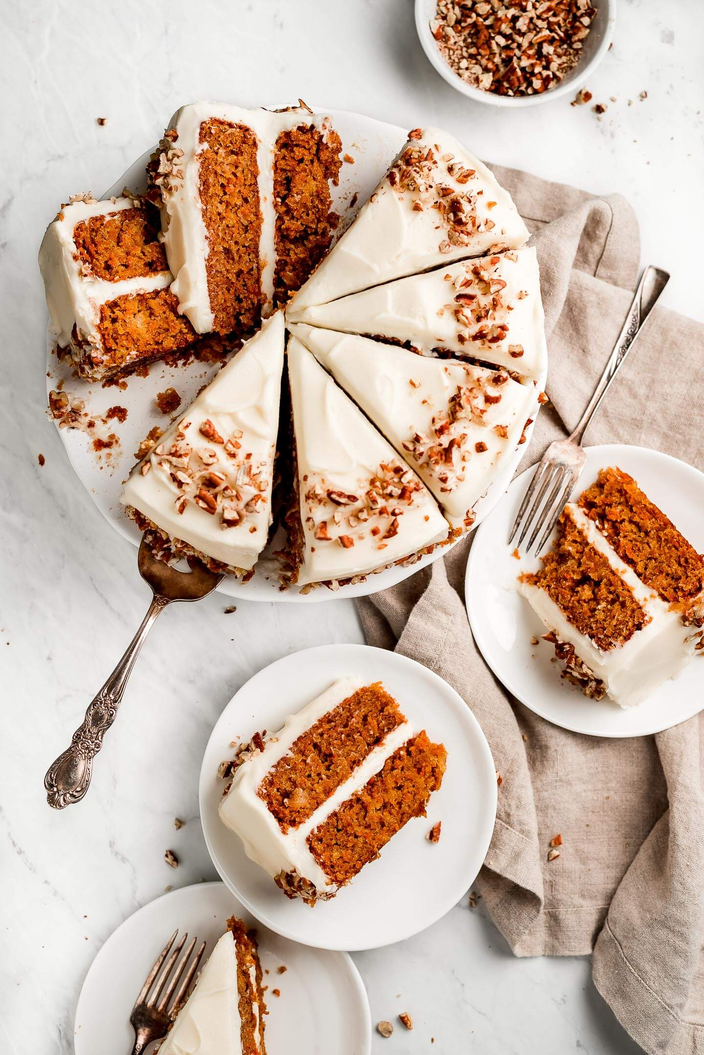 Carrot Cake sliced up on a cake stand and some pieces on plates.