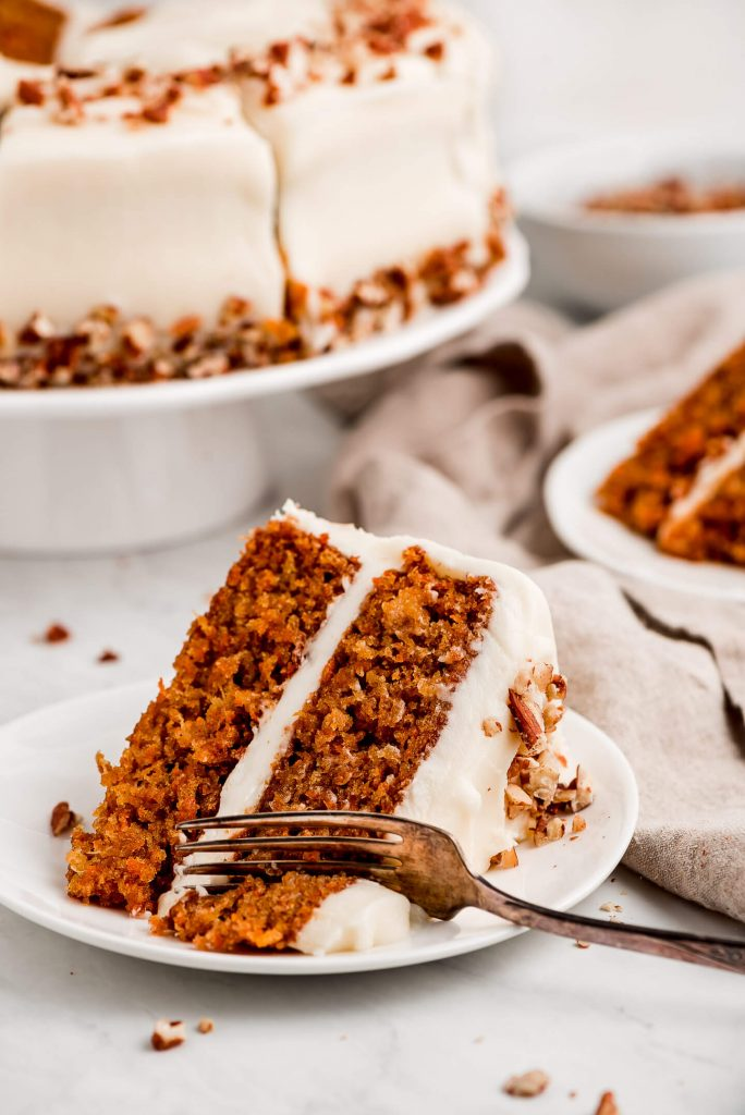 A fork cutting into a slice of Moist Carrot Cake on it's side on a plate.