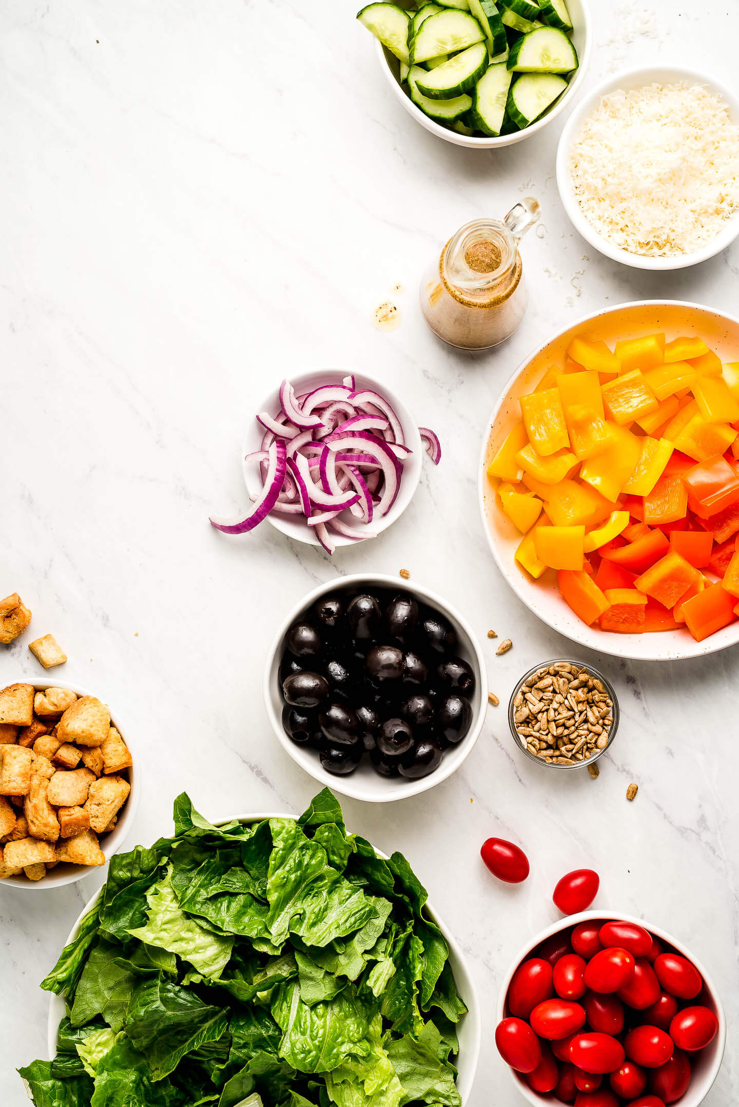 Ingredients on a marble surface in bowls- cucumbers, parmesan cheese, Italian dressing, bell peppers, onions, black olives, seeds, tomatoes, lettuce, and croutons.