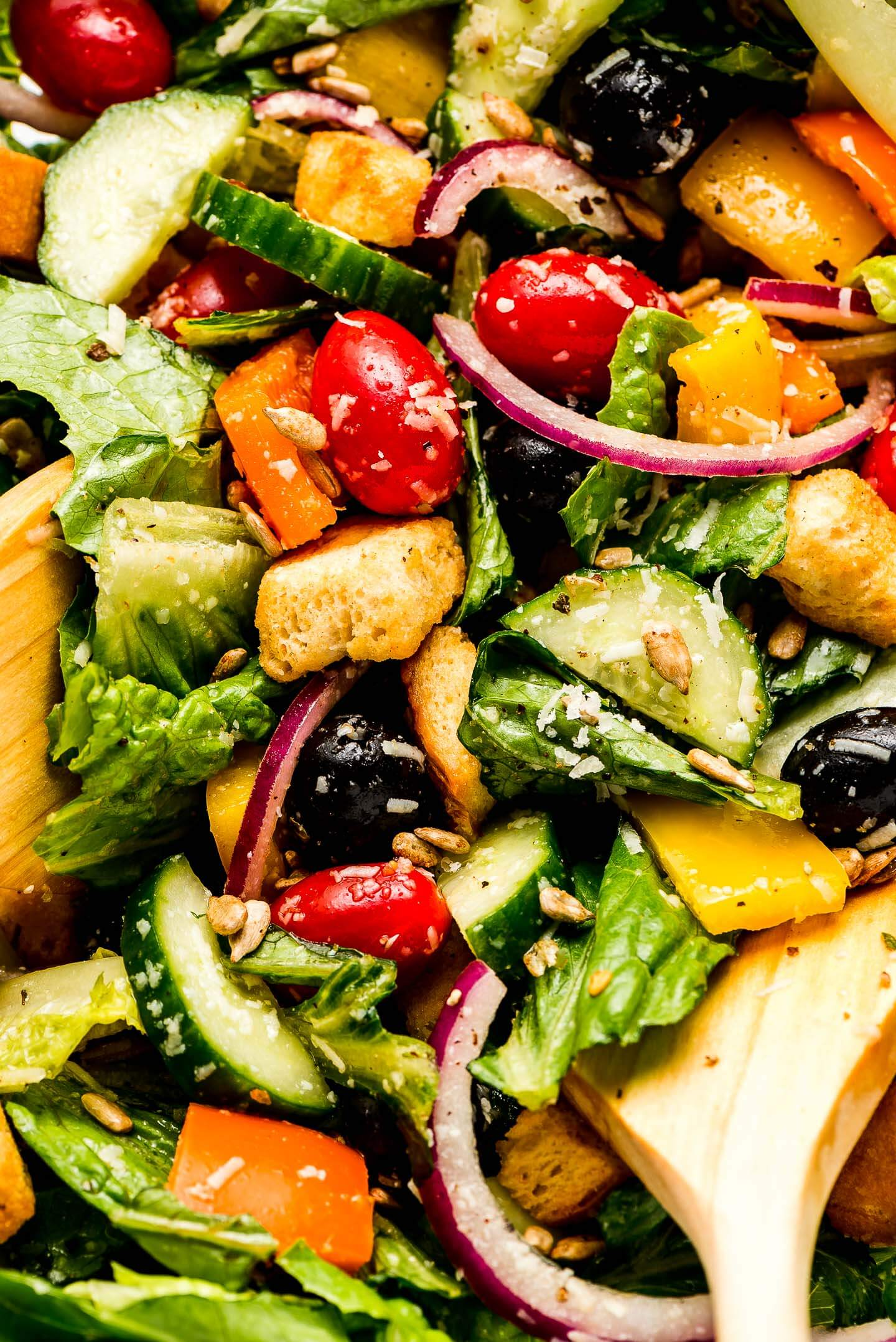 Close up shot of a tossed side salad with romaine lettuce, cucumbers, grape tomatoes, bell peppers, olives, red onion, sunflower seeds, and parmesan cheese.
