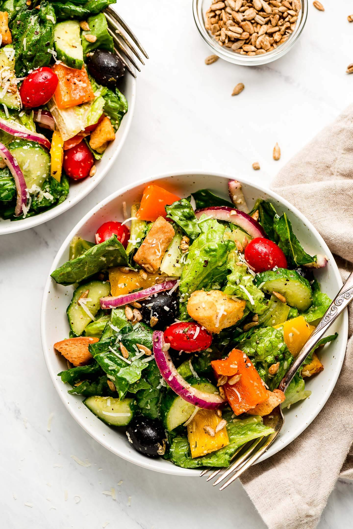 Two bowls of side salads garnished with parmesan cheese.