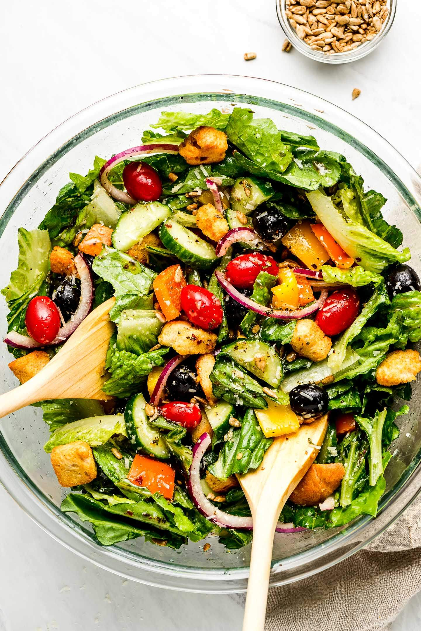 A large bowl of tossed salad comprised of romaine lettuce, olives, cucumbers, peppers, tomatoes, onions, croutons, sunflower seeds, and parmesan cheese.