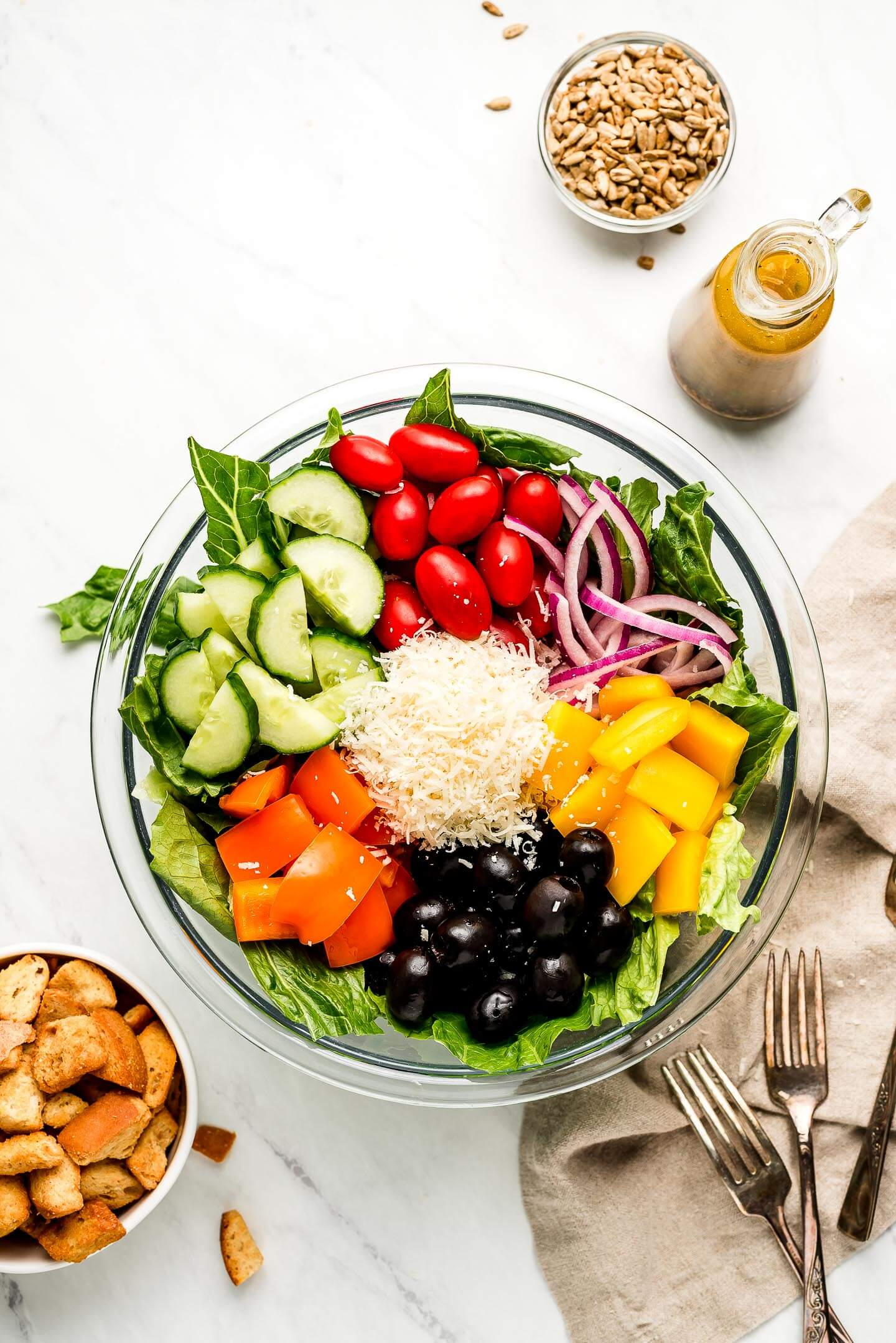 A large bowl of romaine lettuce with olives, cucumbers, peppers, tomatoes, onions, and parmesan cheese on top with bowls of sunflower seeds, croutons, and dressing.