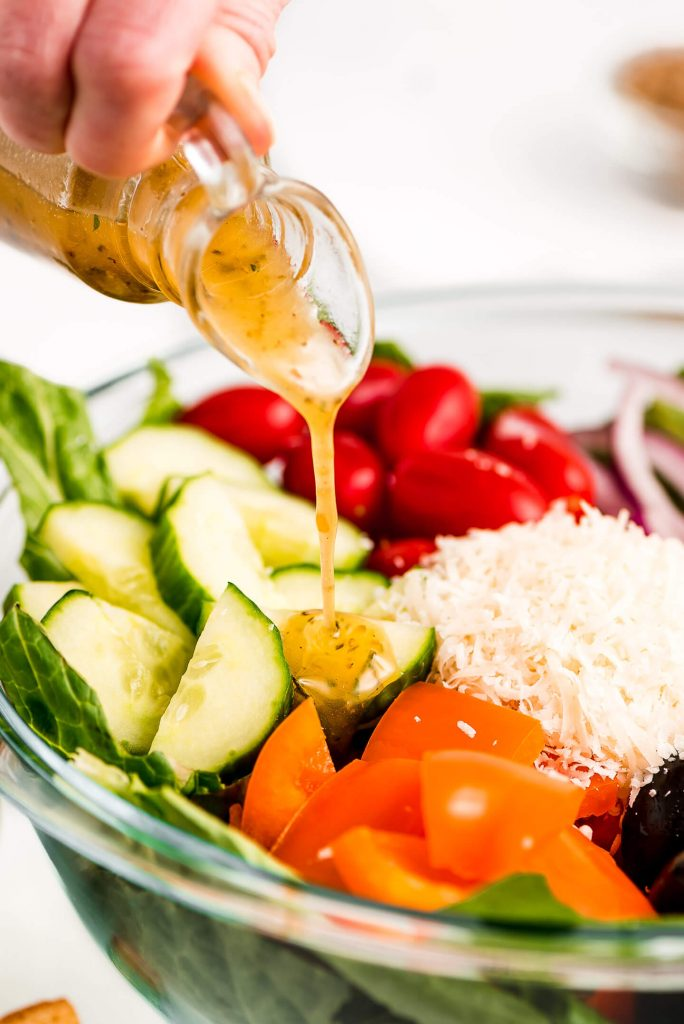 Italian Vinaigrette streaming down from a bottle and onto a salad.