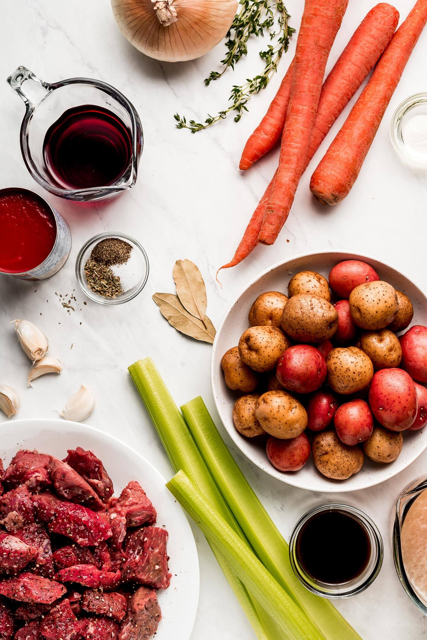 Ingredients on a marble surface- little potatoes, beef, celery, carrots, wine, onion, thyme, tomato sauce, garlic, and spices.