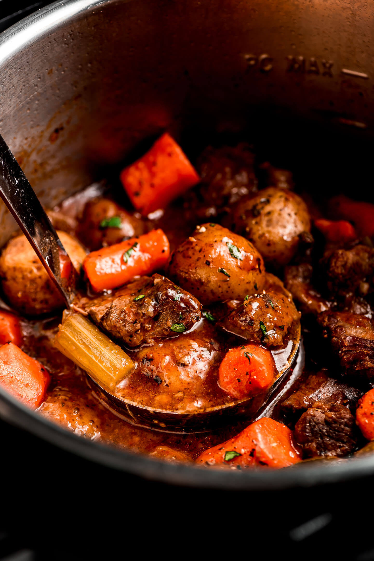 Close up of a ladle of Beef Stew in a pot.