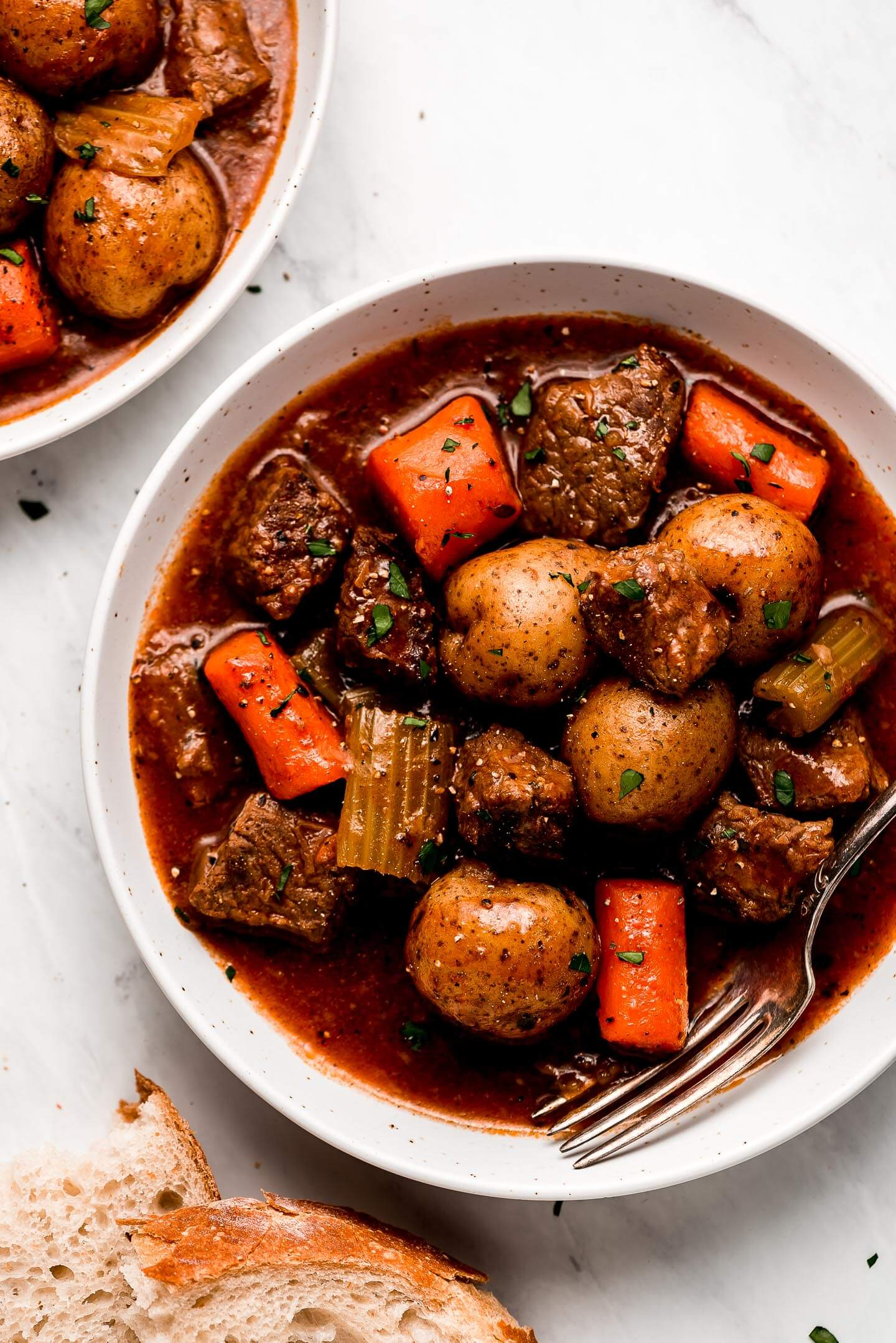 Two bowls of Beef Stew with bread to the side for dipping.