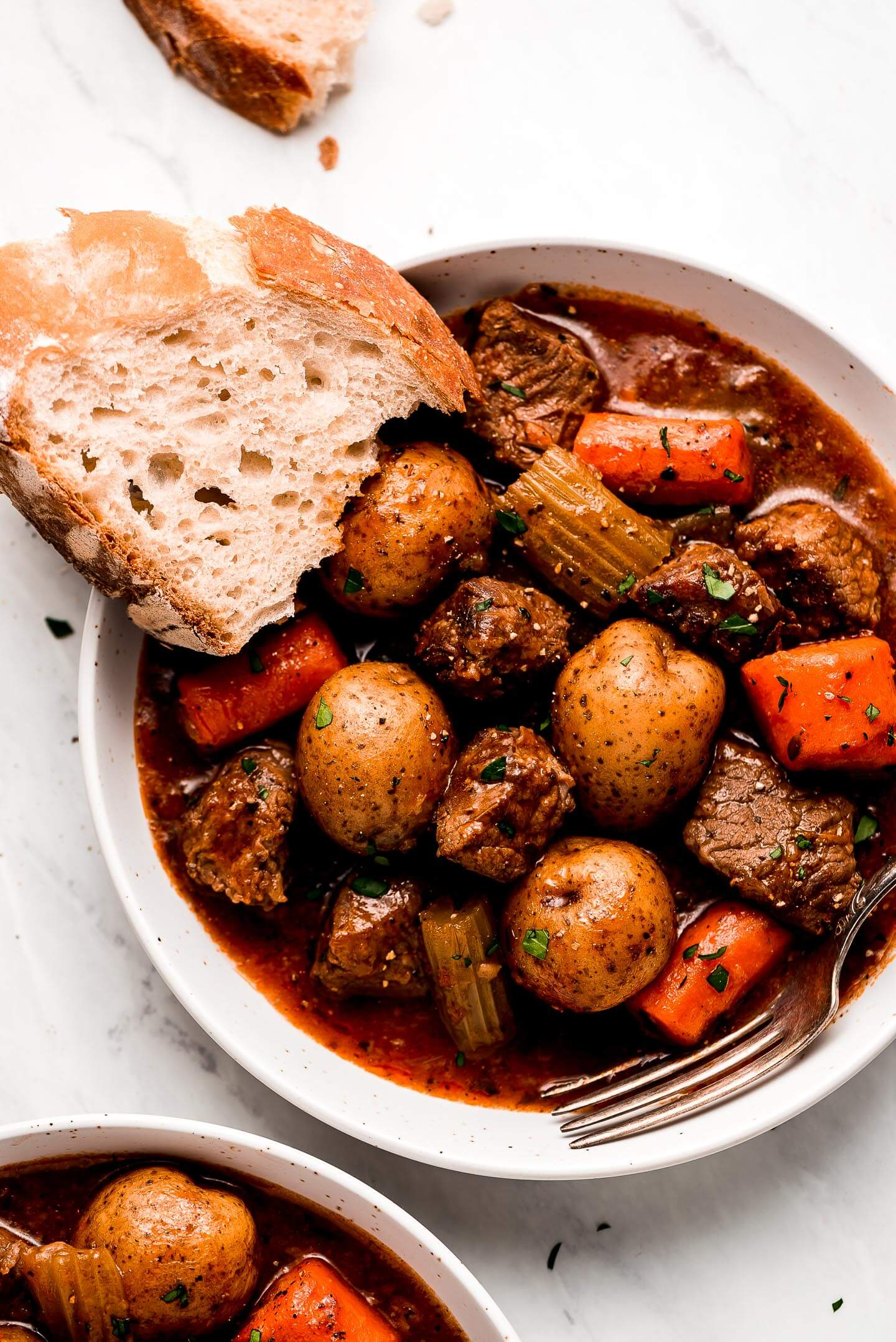 A bowl of Instant Pot Beef Stew with a slice of artisan bread on the side.