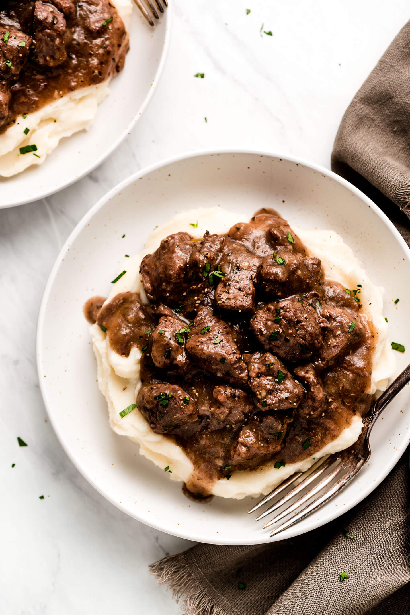 Two bowls of bite size pieces of beef with gravy over mashed potatoes.