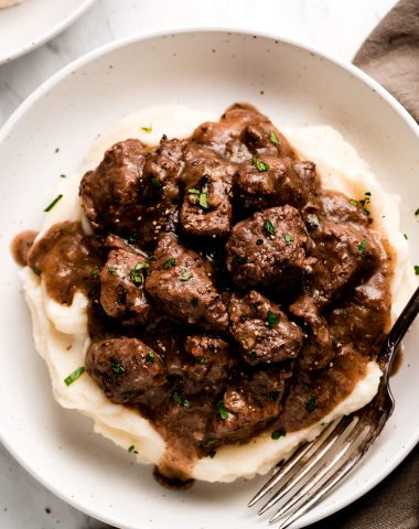 A bowl of Beef Tips and Gravy over mashed potatoes and garnished with fresh parsley.