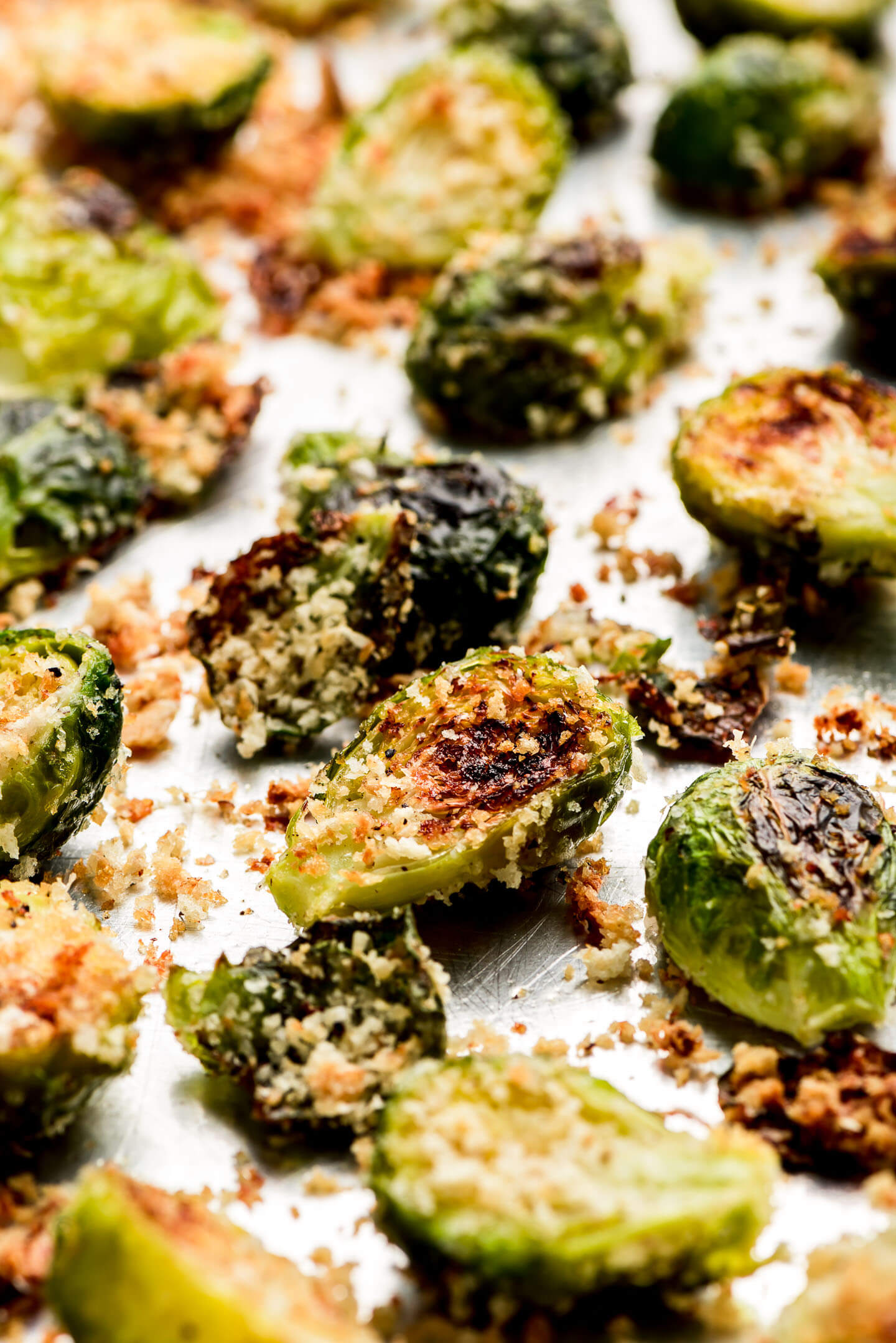 Roasted Brussels Sprouts coated in crispy panko and parmesan on a baking sheet.