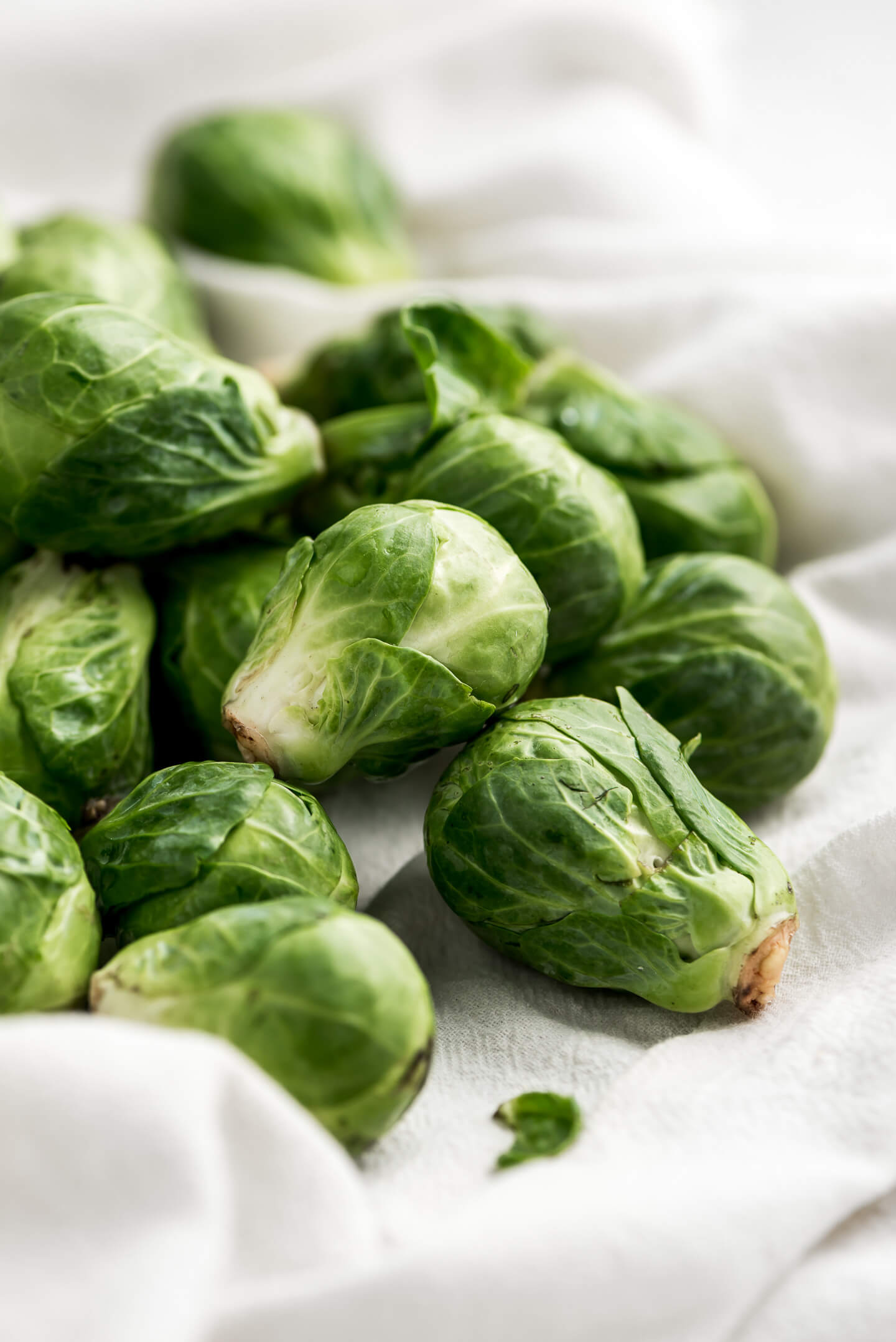 Raw brussels sprouts on a white tea towel.