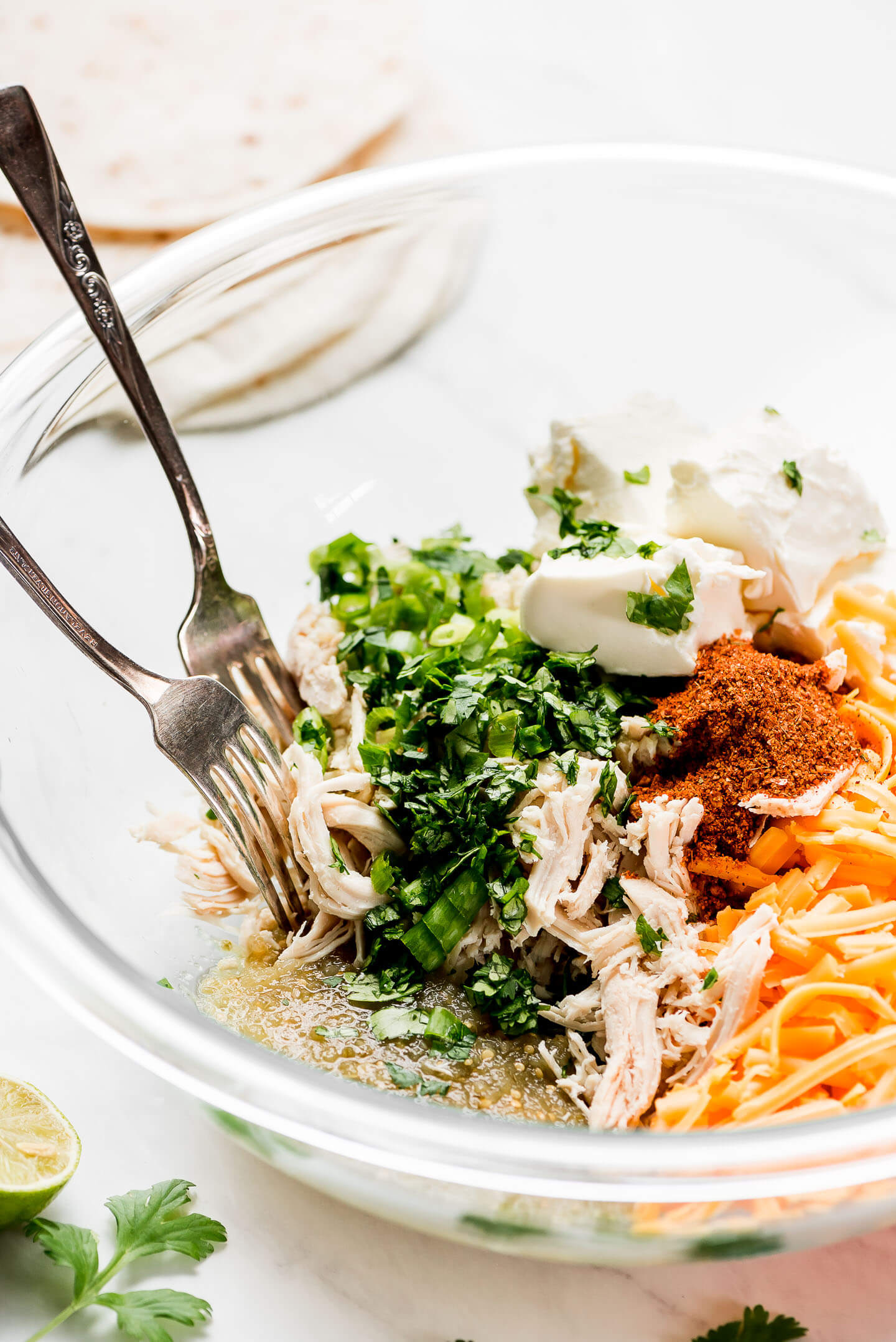 A large glass mixing bowl with shredded chicken, salsa verde, cheese, cilantro, green onions, cream cheese, and taco seasoning.