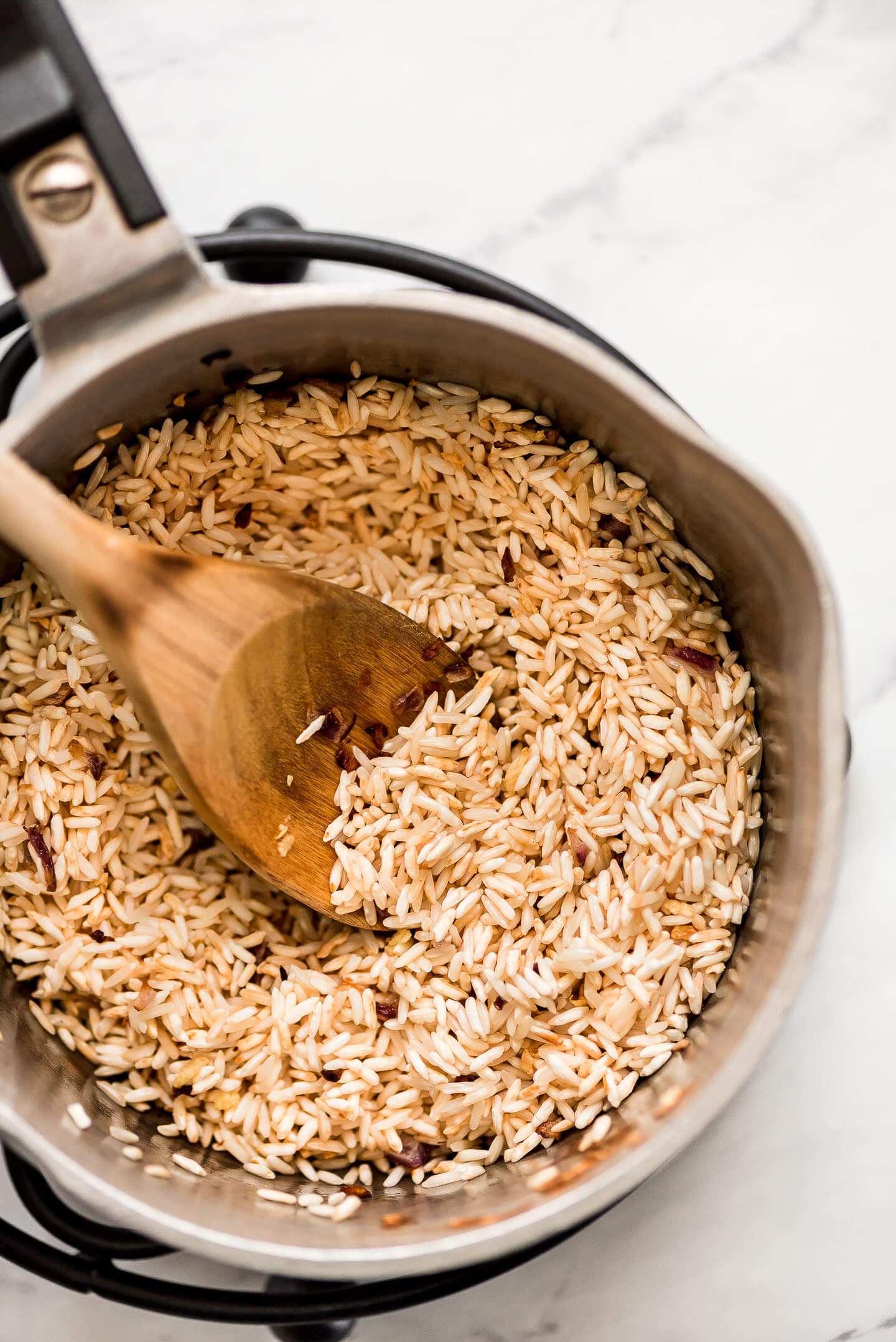 Browned rice in a pot with a wooden spoon.