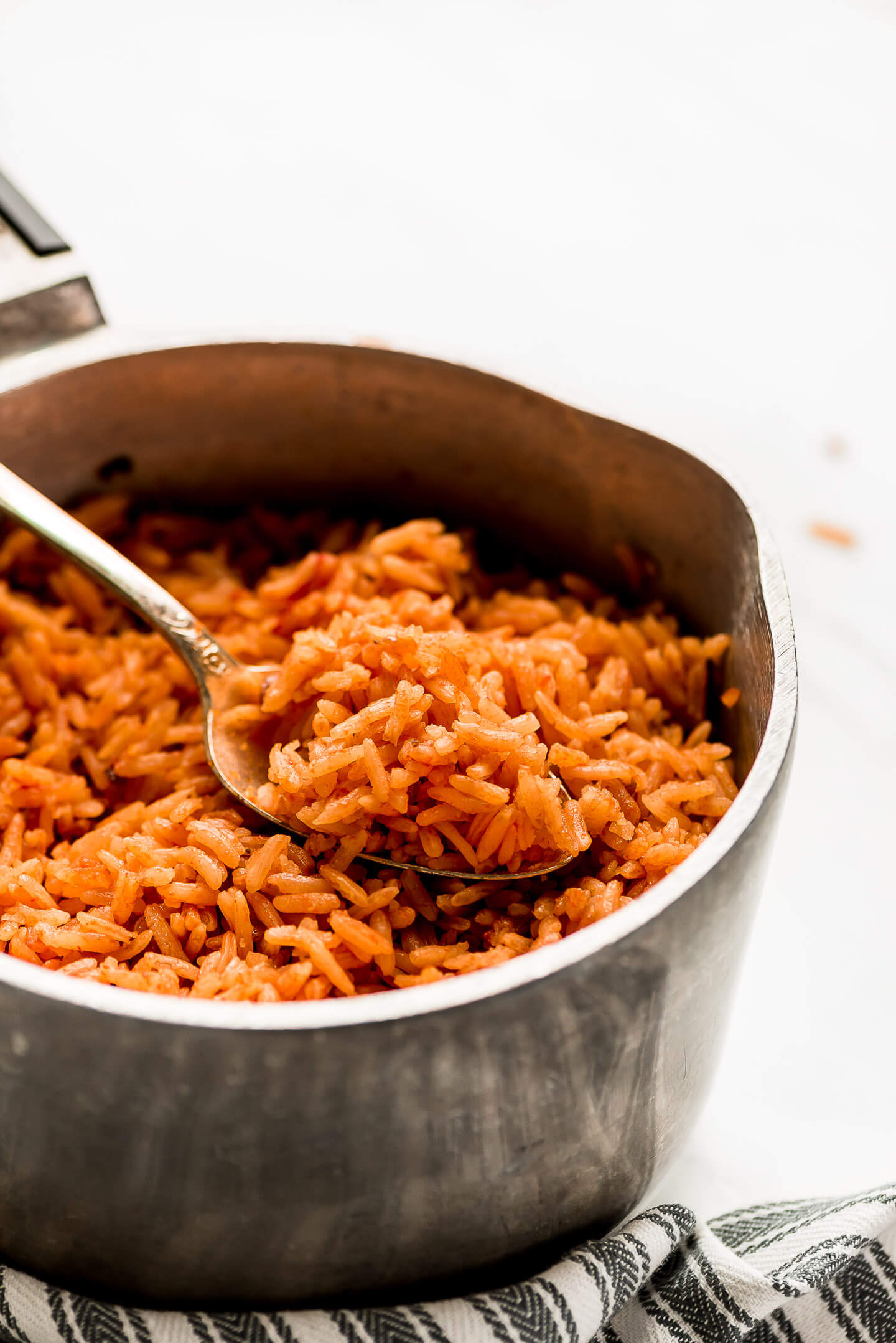A spoonful of Spanish Rice in a pot.