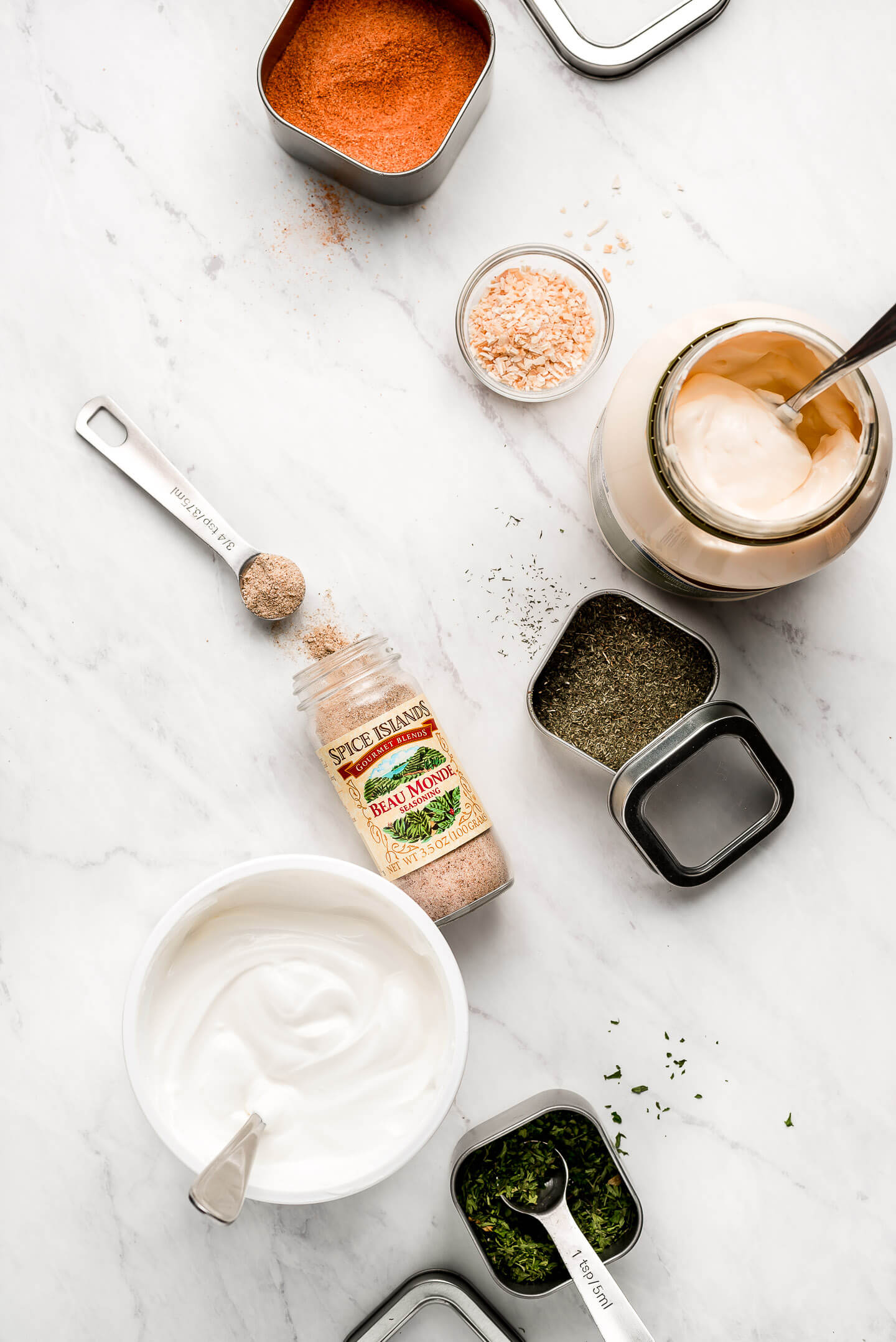 Ingredients on a marble surface- spices, herbs, mayo, and sour cream.