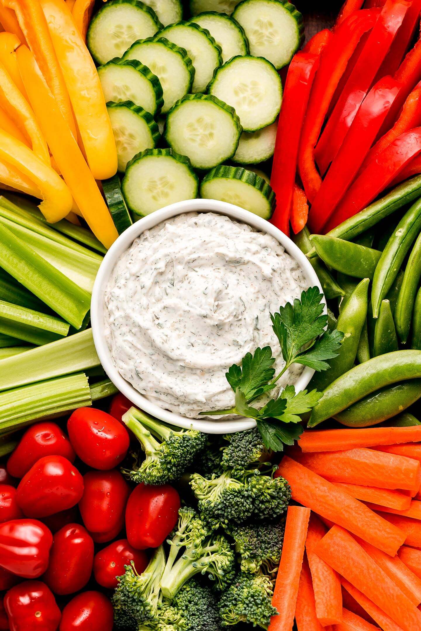 A bowl of creamy Veggie Dip surrounded by fresh vegetables.