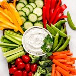 A large platter with a bowl Veggie Dip and sliced fresh vegetables- bell peppers, cucumbers, snap peas, carrots, broccoli, celery, and grape tomatoes.