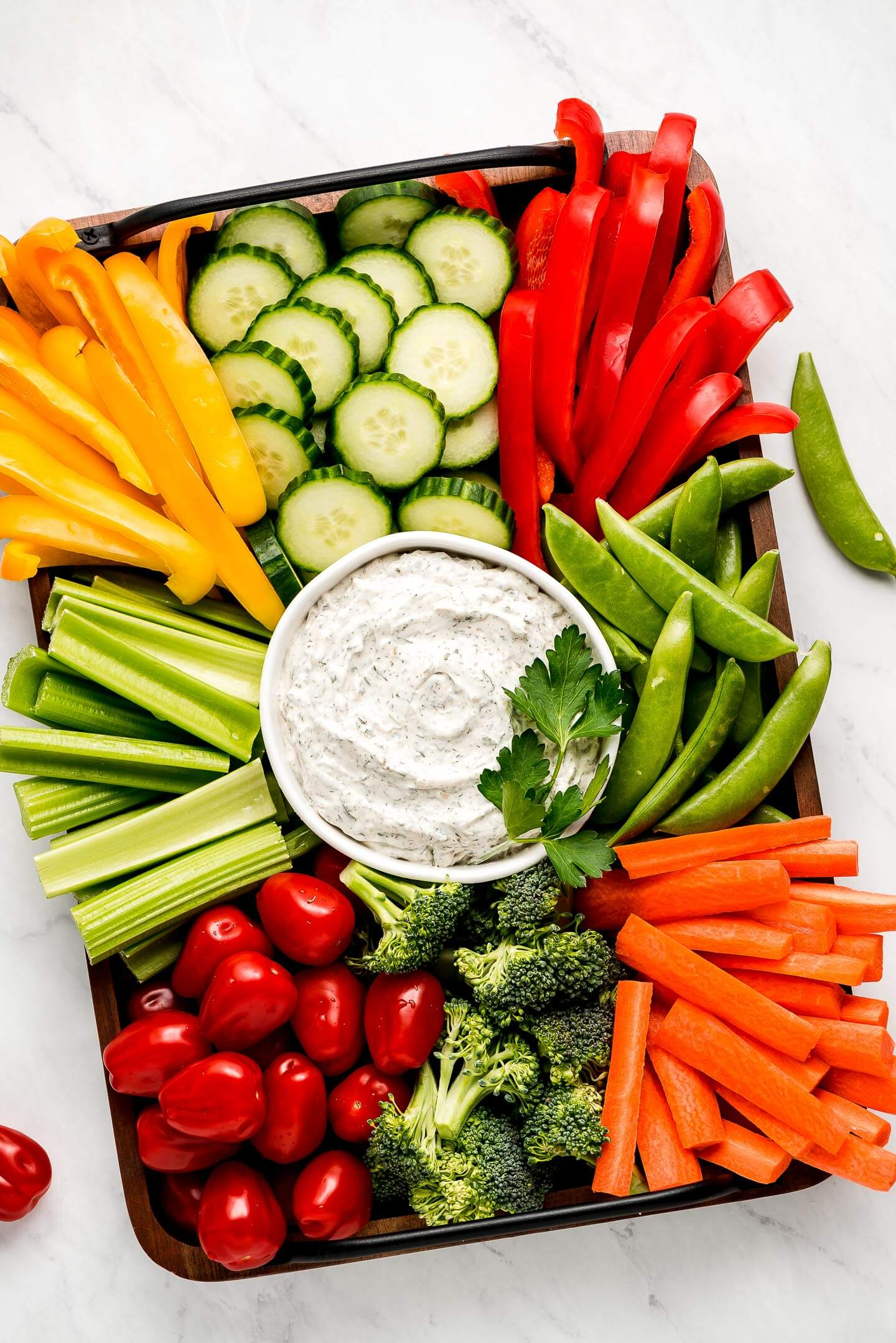 A large platter with a bowl Vegetable Dip and sliced fresh vegetables- bell peppers, cucumbers, snap peas, carrots, broccoli, celery, and grape tomatoes.