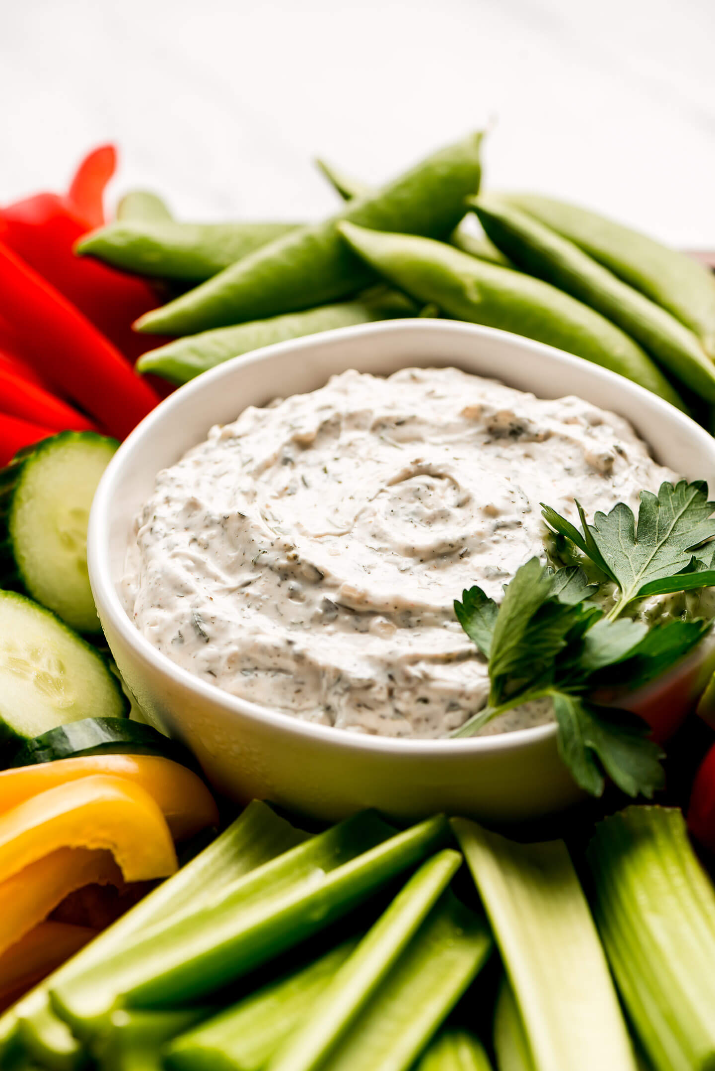 A close up shot of a bowl of seasoned sour cream and mayonnaise condiment.