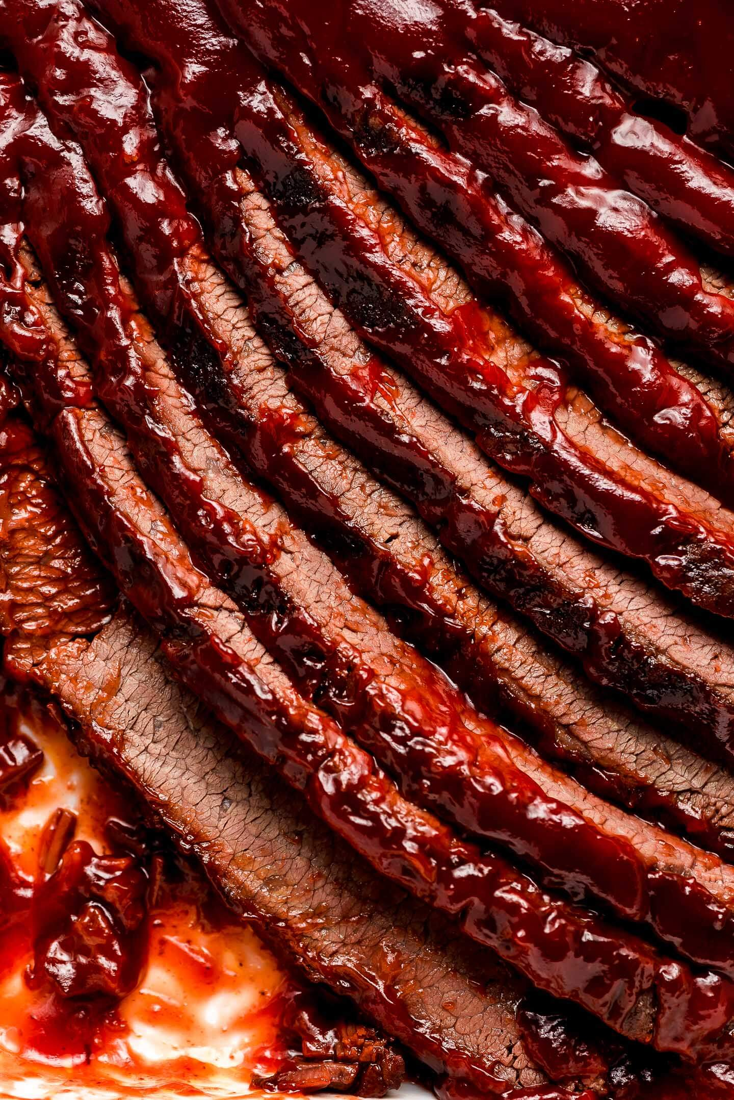 Slices of brisket in a pan covered in barbecue sauce.