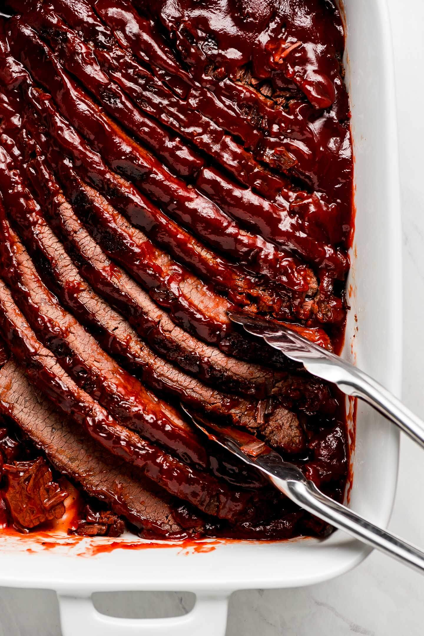 Tongs grabbing slices of barbecue Brisket from a pan.