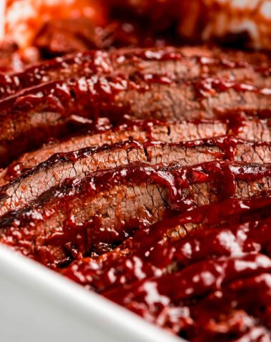 Close up shot of sliced Beef Brisket with barbecue sauce on the top edges.
