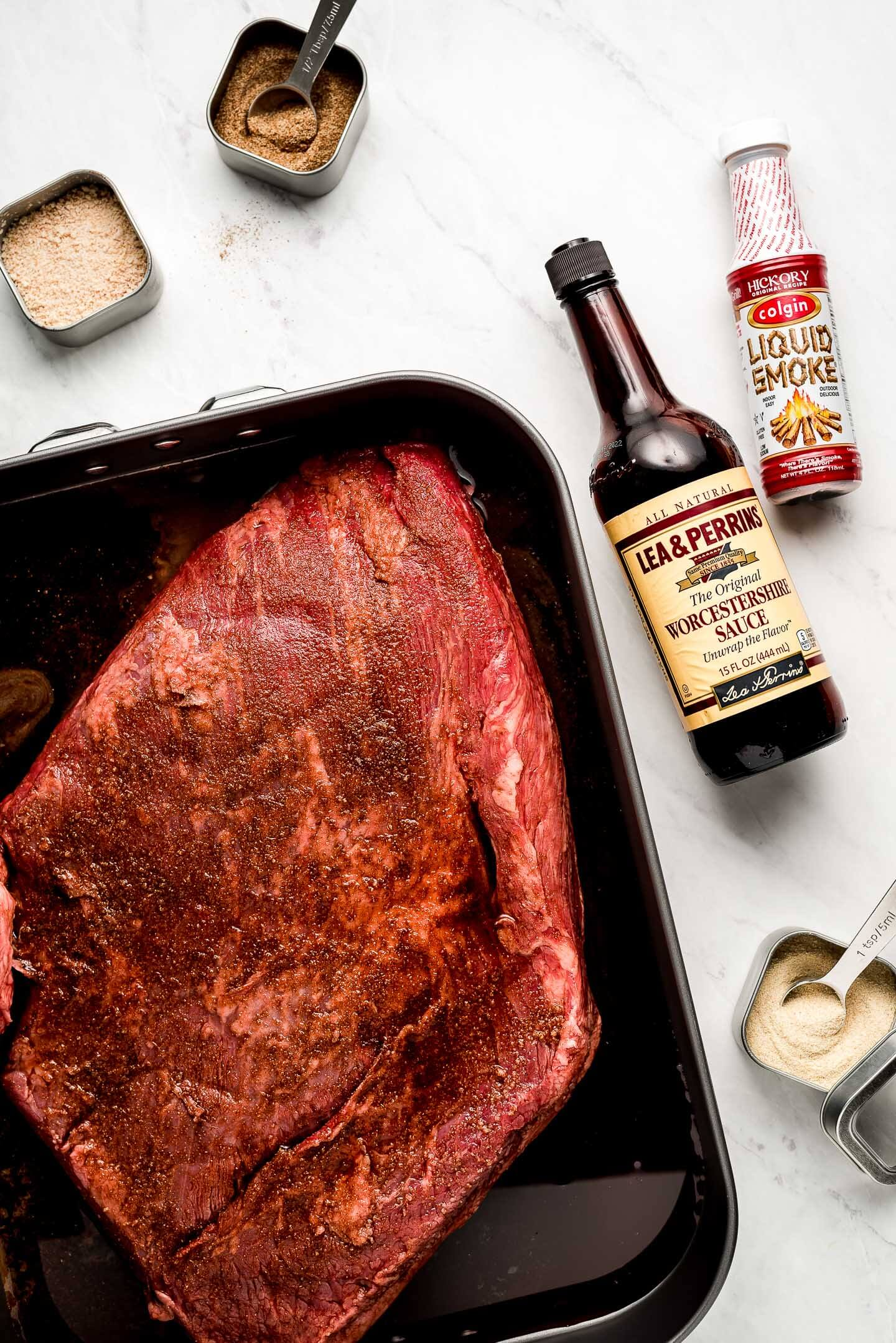 Ingredients on a marble surface- brisket, spices, Worcestershire sauce, and liquid smoke.