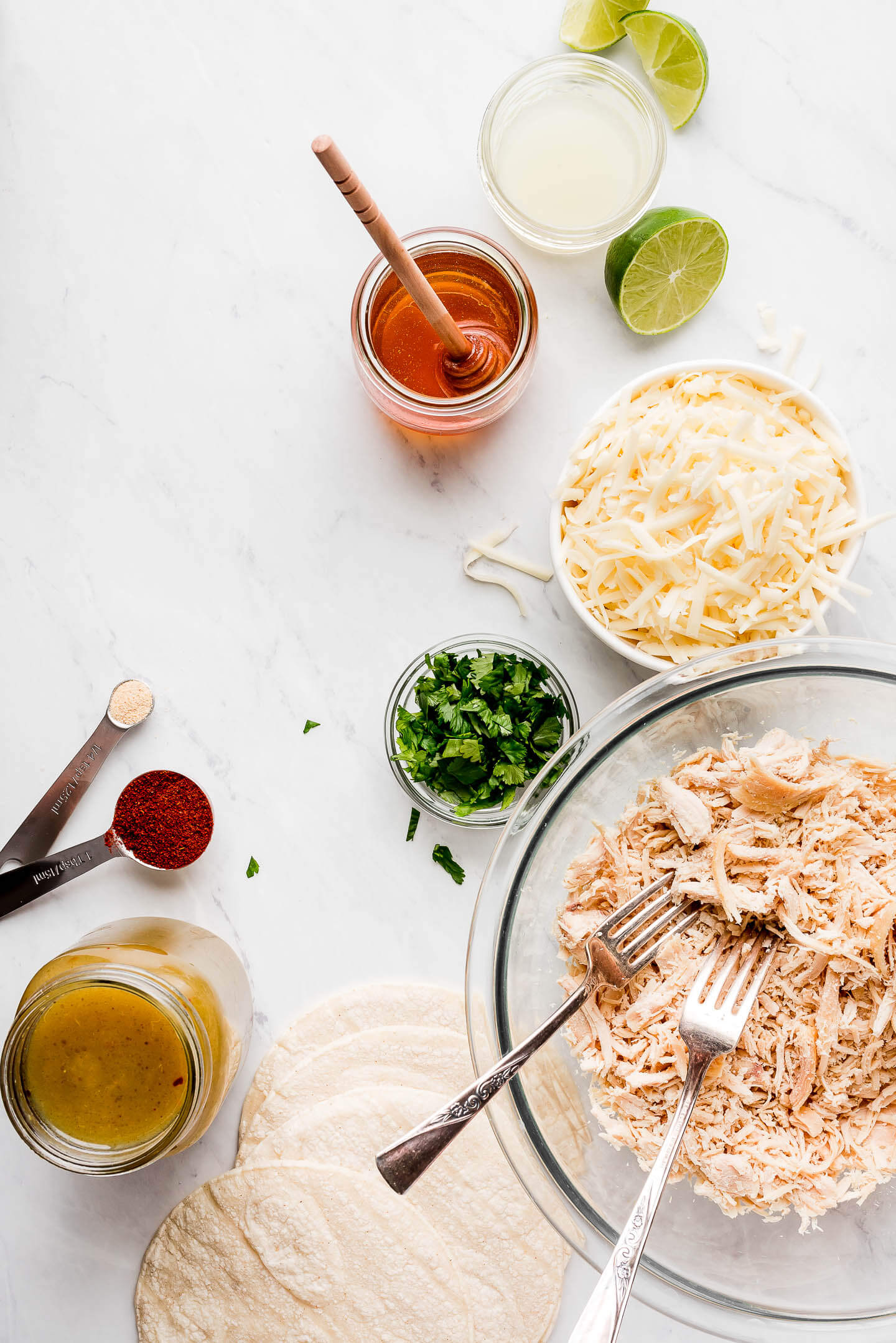 Ingredients on a marble surface- lime juice, honey, shredded cheese, cilantro, shredded chicken, corn tortillas, spices, green sauce.