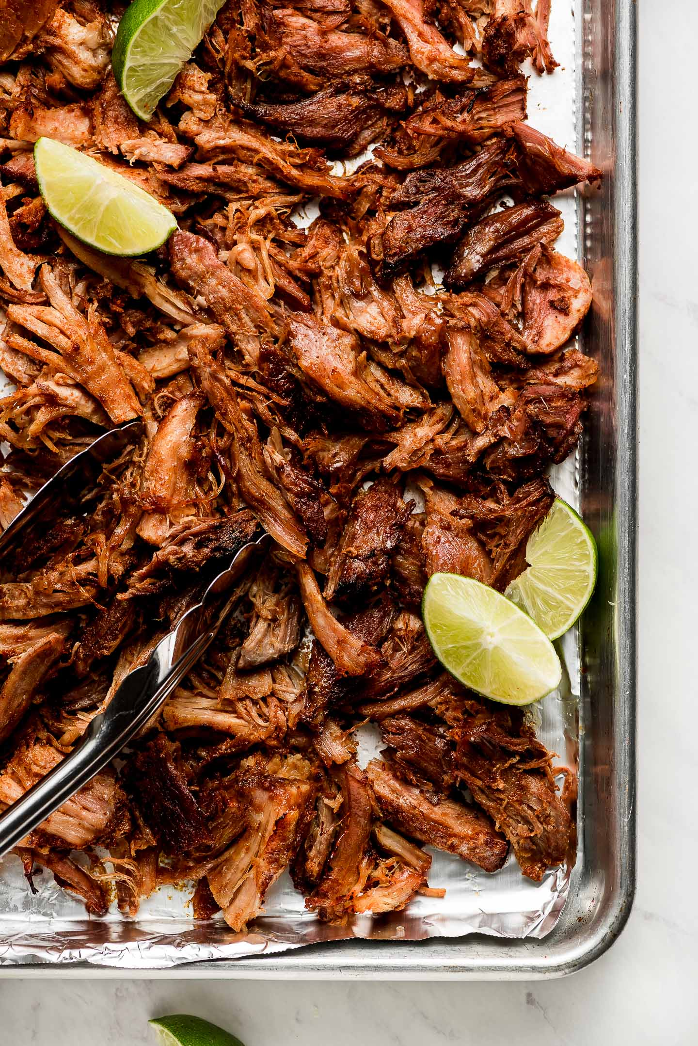 Crispy Slow Cooker Carnitas on a baking sheet with lime wedges.