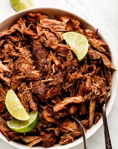 Pork Carnitas in a large white bowl garnished with lime wedges.