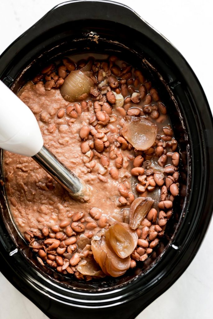 Puréeing pinto beans in a Crock-Pot using a hand blender.