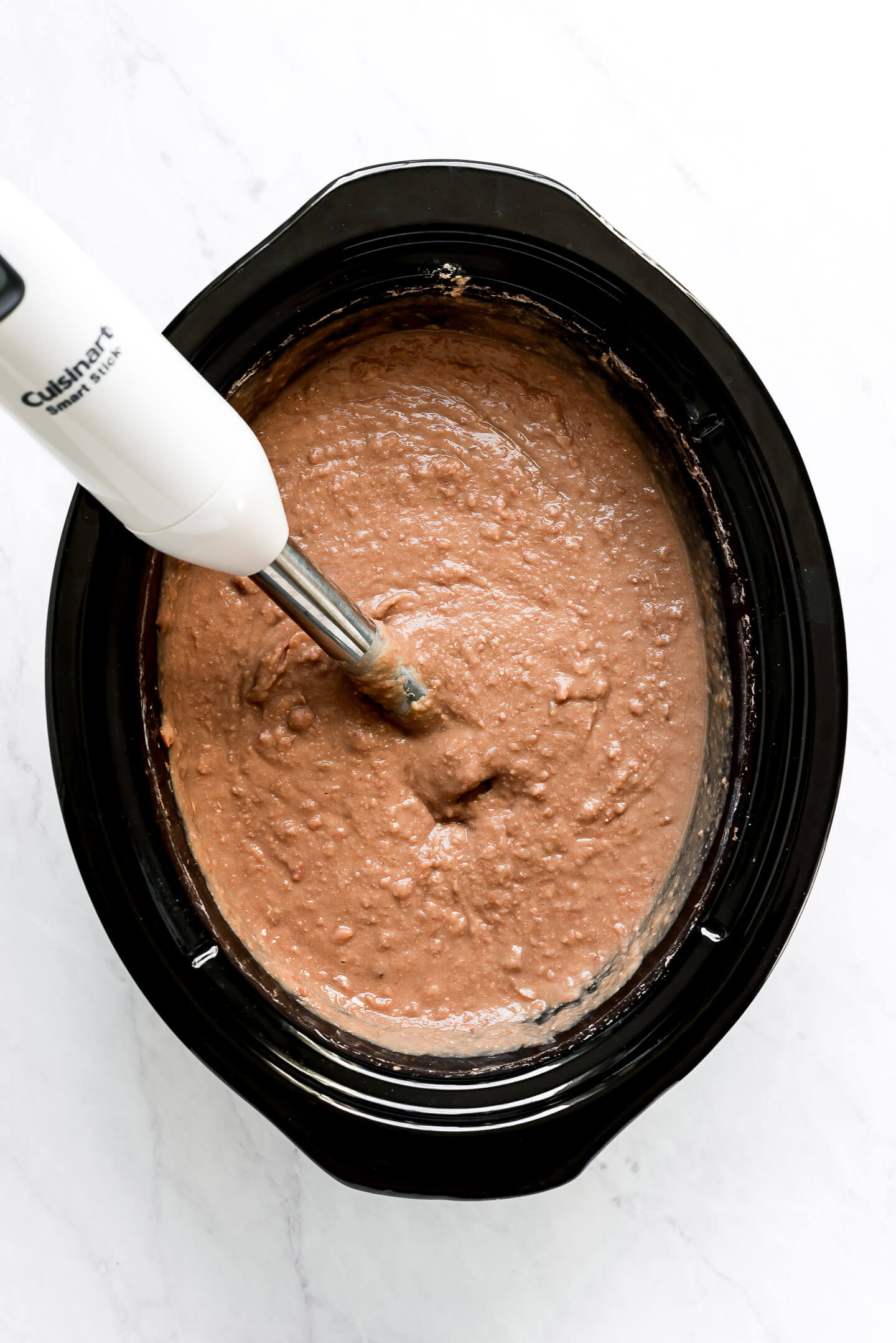A slow cooker full of mashed pinto beans with a hand blender in it.