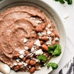 Slow Cooker Refried Beans in a bowl, garnished with pinto beans, queso fresco, and cilantro.