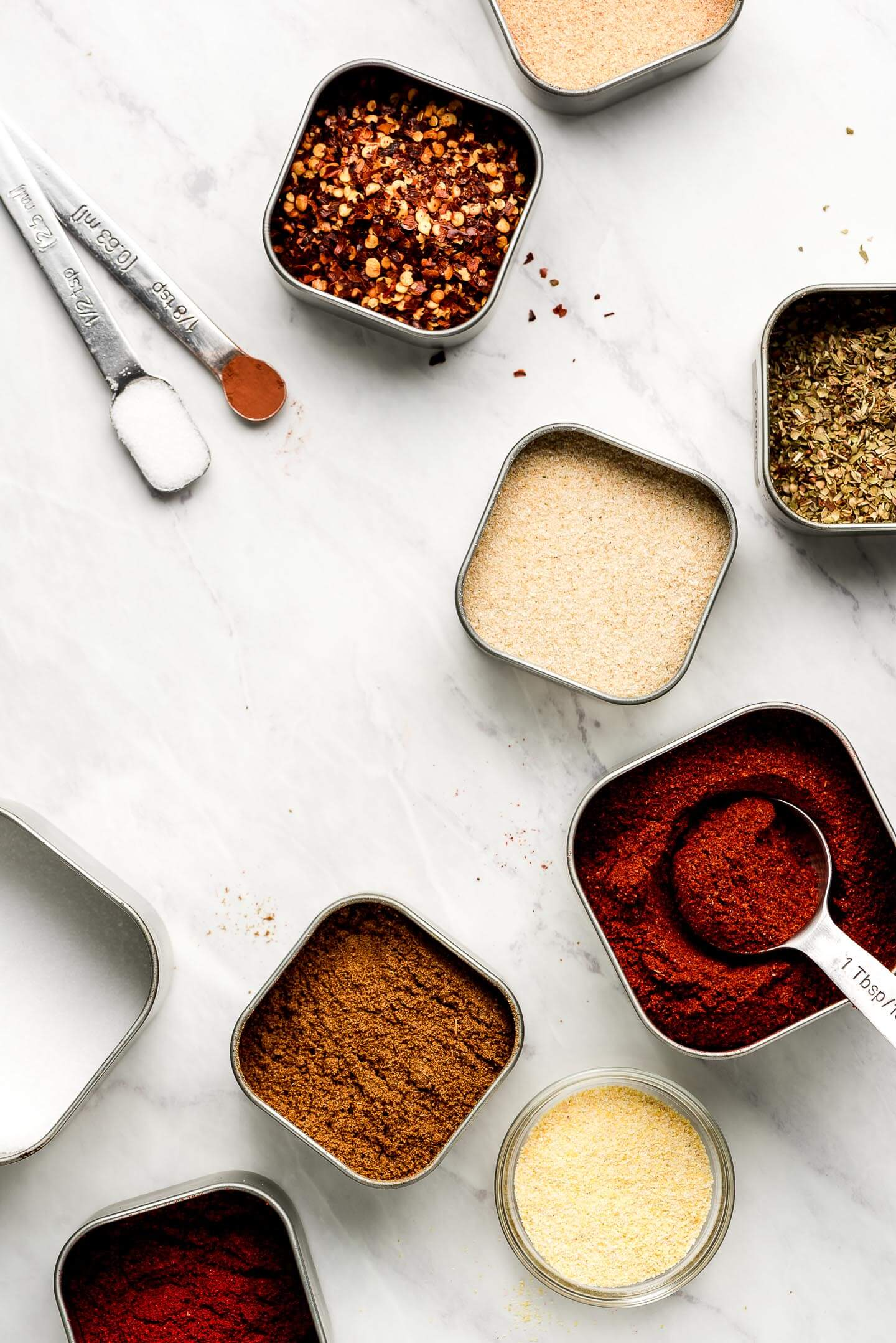 Various tins of spices and measuring spoons on a marble surface.