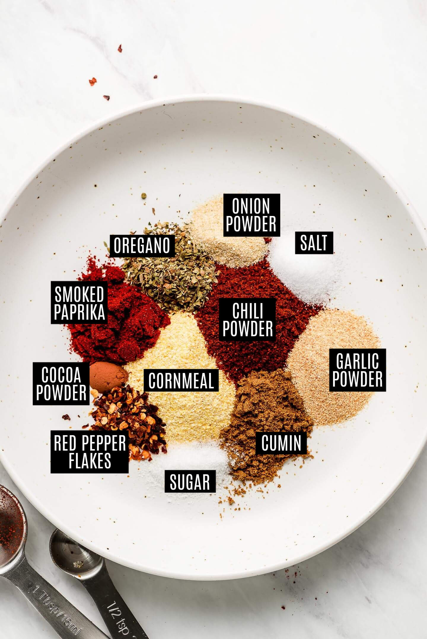 Various spices in a shallow white bowl for Taco Seasoning.