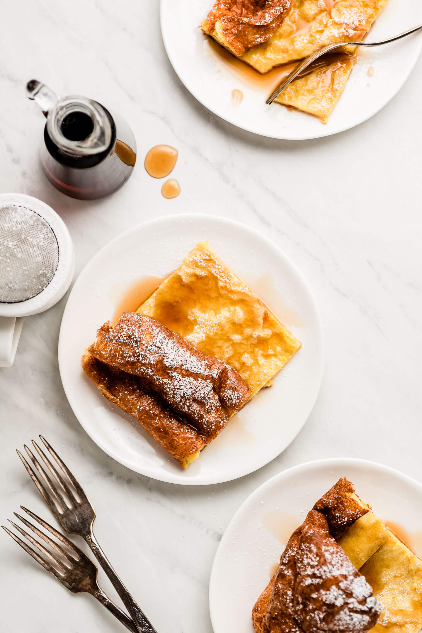Plates of slices of German Pancakes topped with syrup and powdered sugar with syrup and powdered sugar to the sides.