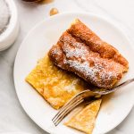 A fork cutting into in a piece of German Pancake covered in syrup and powdered sugar.