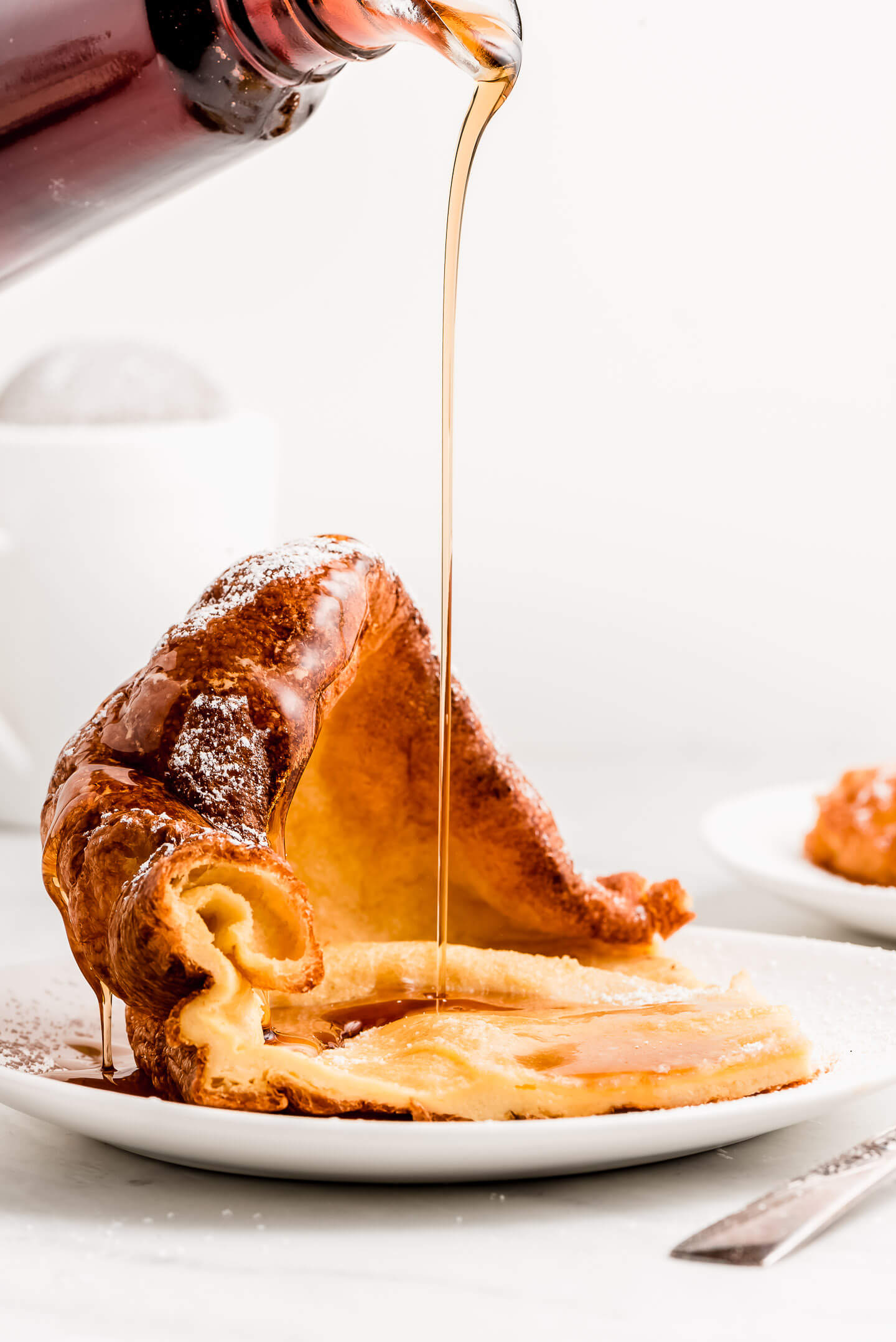 Syrup streaming down onto a slice of German Pancakes.